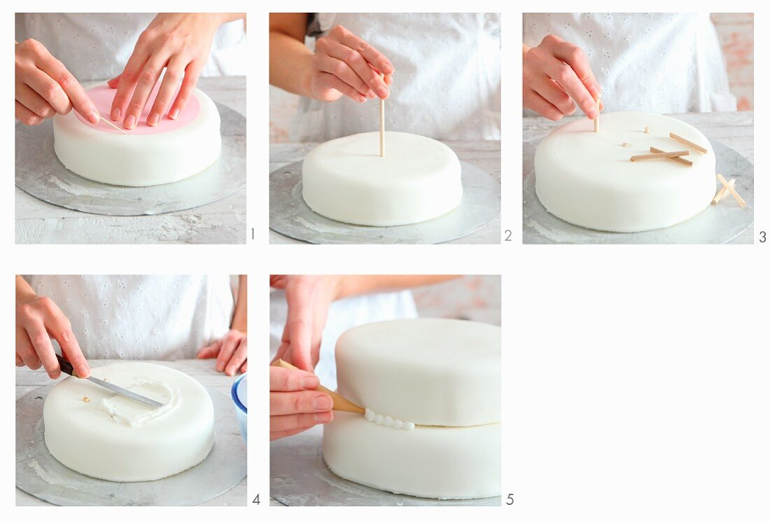 A multi-tier cake being decorated with fondant icing