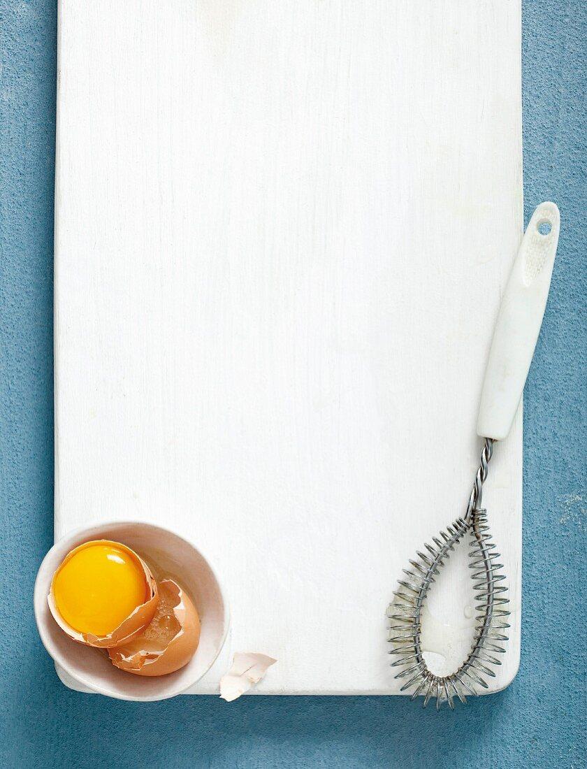 An arrangement featuring a broken egg and a whisk