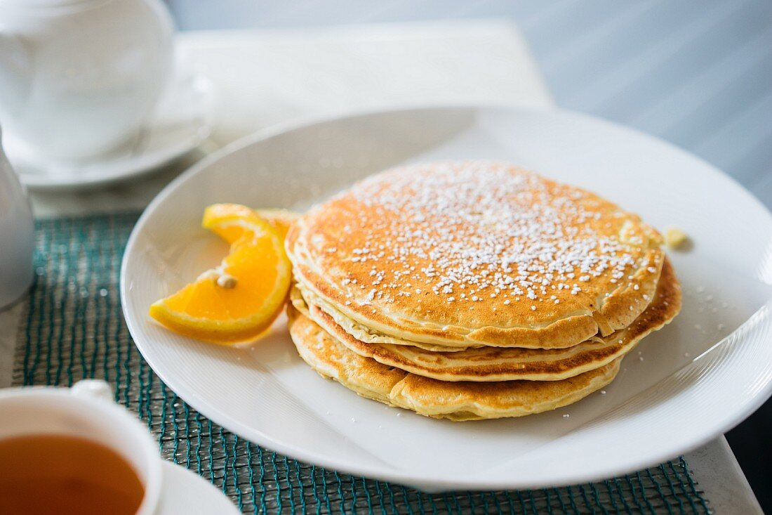 A stack of pancakes dusted with icing sugar and serve with orange slices