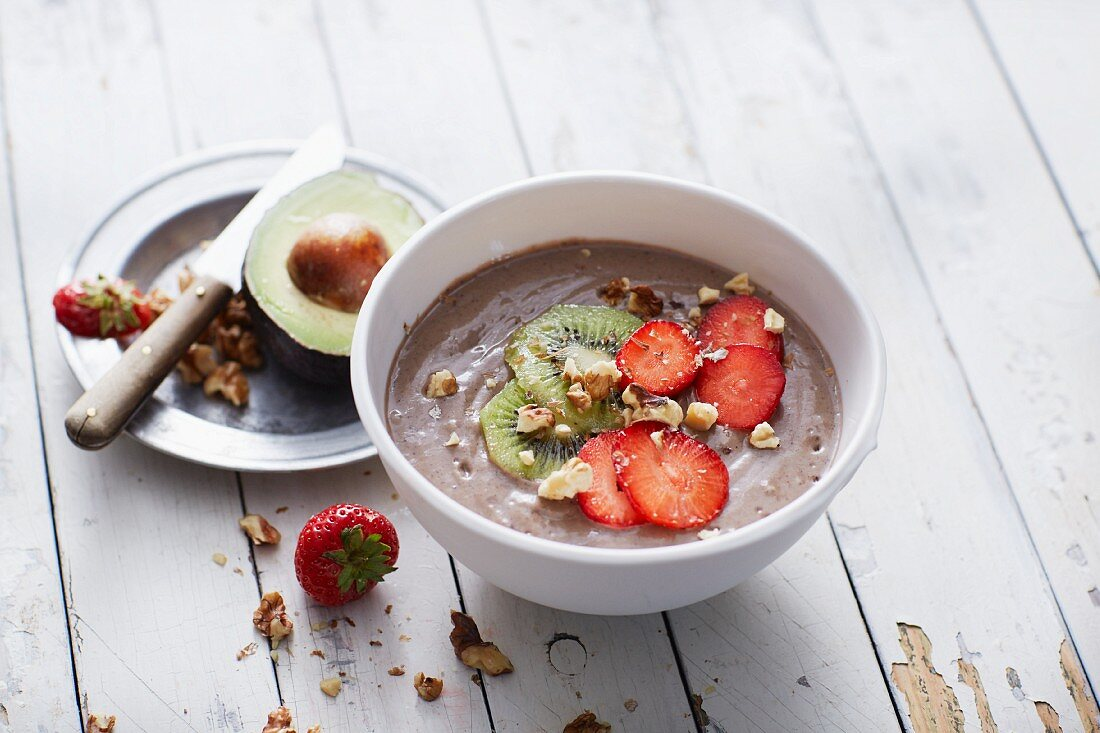 A bowl of avocado smoothie with strawberries and kiwi
