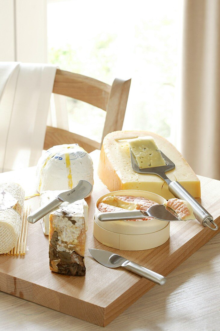 Various cheeses on a wooden chopping board