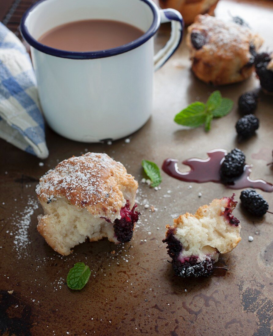 Freshly baked mulberry muffins, broken, with a cup of coffee