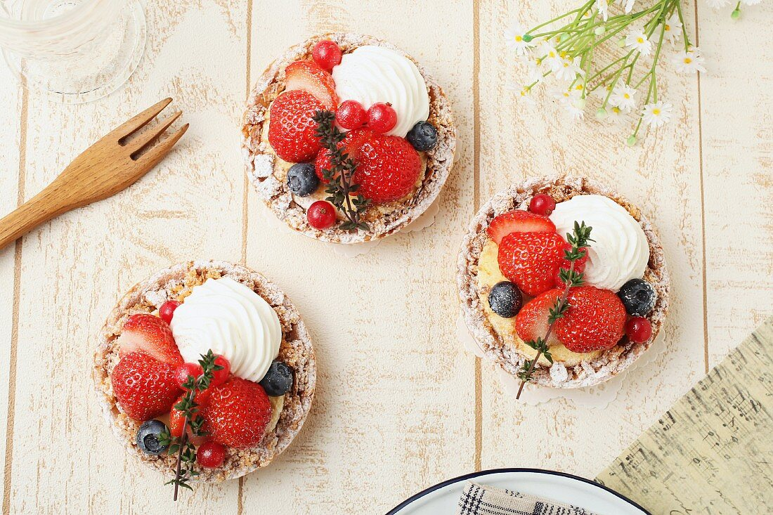 Strawberry tartlets with blueberries, redcurrants and cream (seen from above)