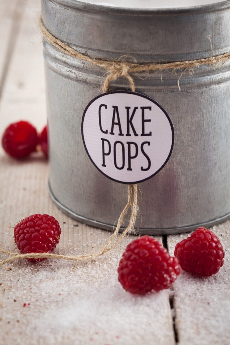 A metal tin of sugar for cake pops with raspberries
