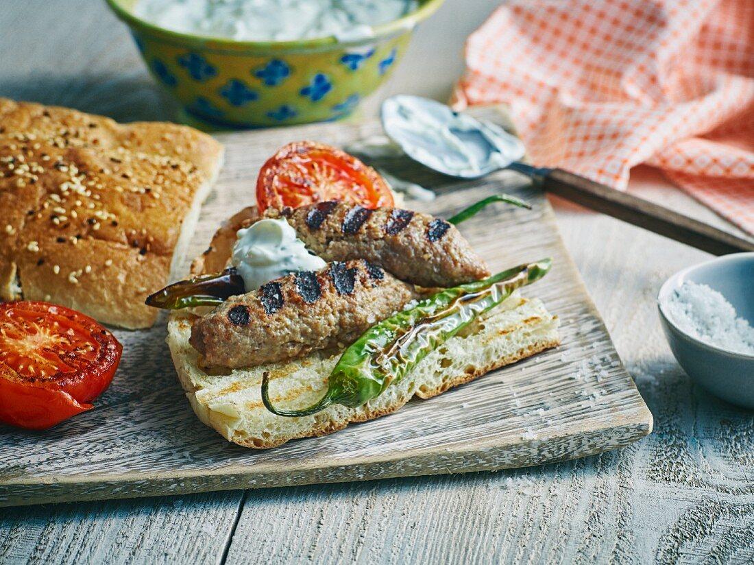 Grilled minced meat kebabs with unleavened sesame seed bread