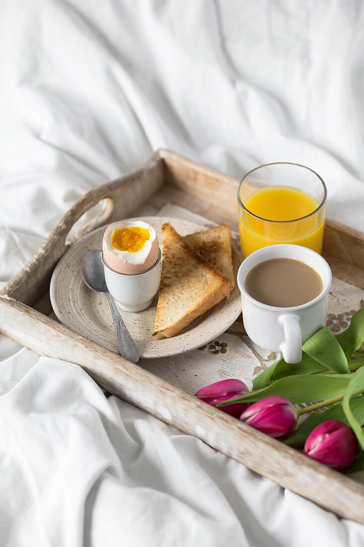 A breakfast tray in bed with a soft-boiled egg, toast, coffee and orange juice for Mother's Day