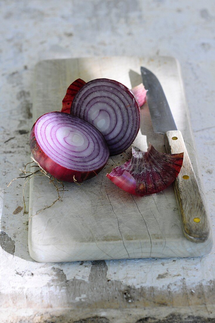 A red onion, halved, with a knife on a chopping board
