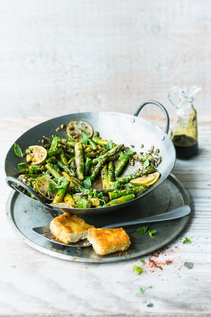 Stir-fried green asparagus with crispy feta cheese, limes and mint