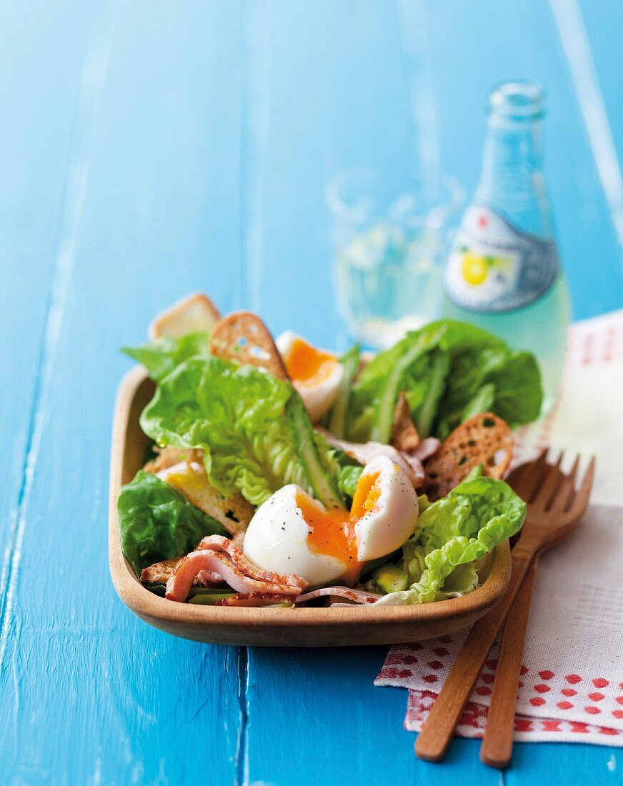 A salad with a soft-boiled egg, bacon and green asparagus