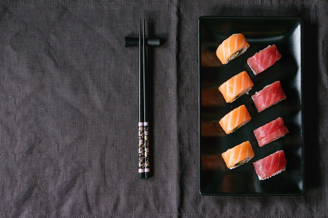 Sushi with salmon and tuna fish on a black plate next to chopsticks (Japan)
