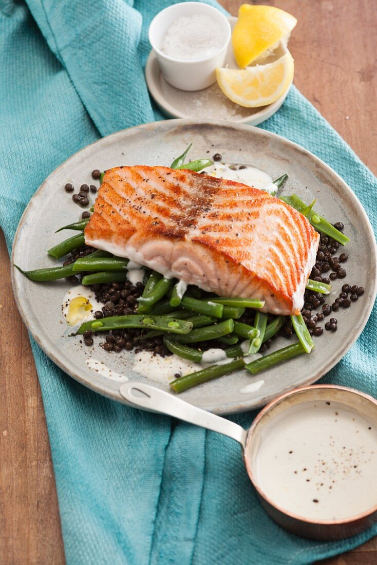 Fried salmon fillet with beluga lentils, beans and lemon sauce