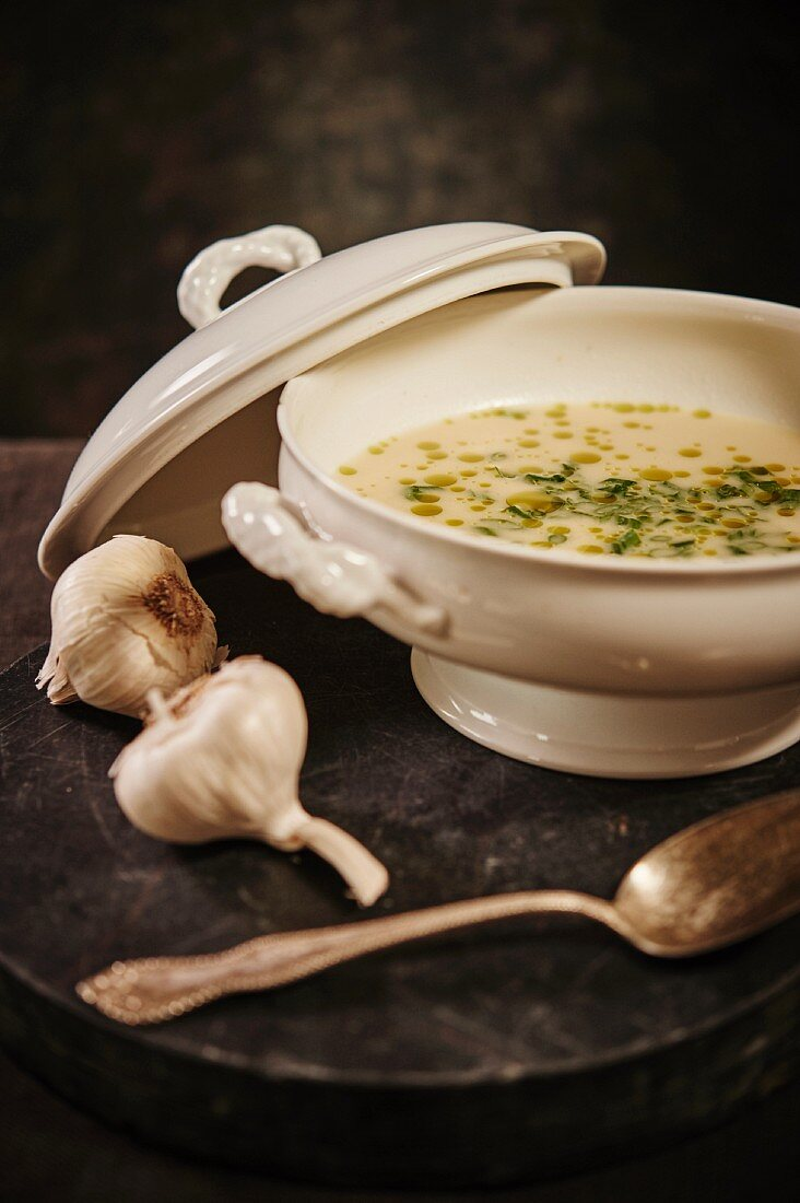 Garlic soup with green onions and herb oil in a soup terrine