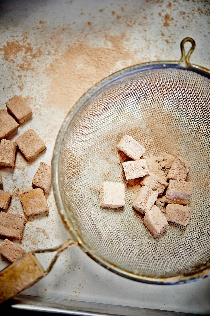 Marshmallows being dusted with cocoa powder