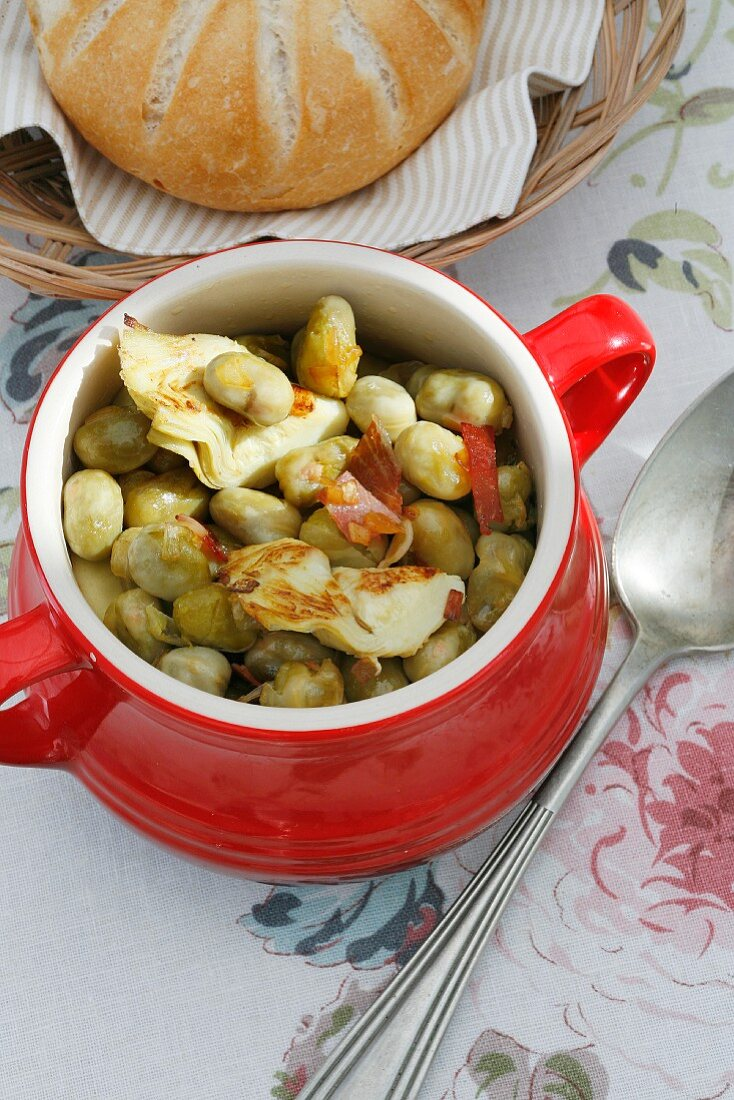 Bean stew with artichoke hearts and bacon strips