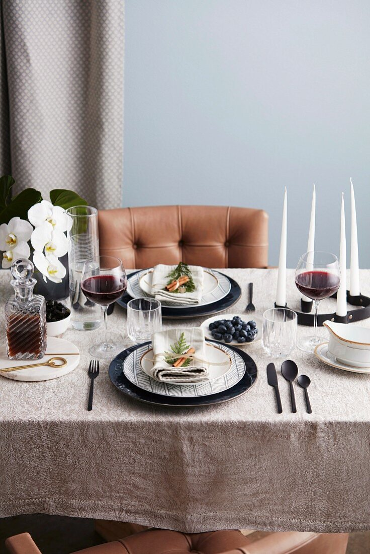 Laid table with black cutlery, red wine glasses, candles and orchids