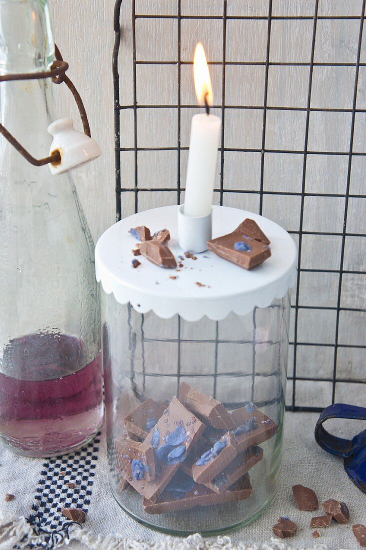 Chocolate with violets in storage jar with candle on top next to bottle of violet syrup