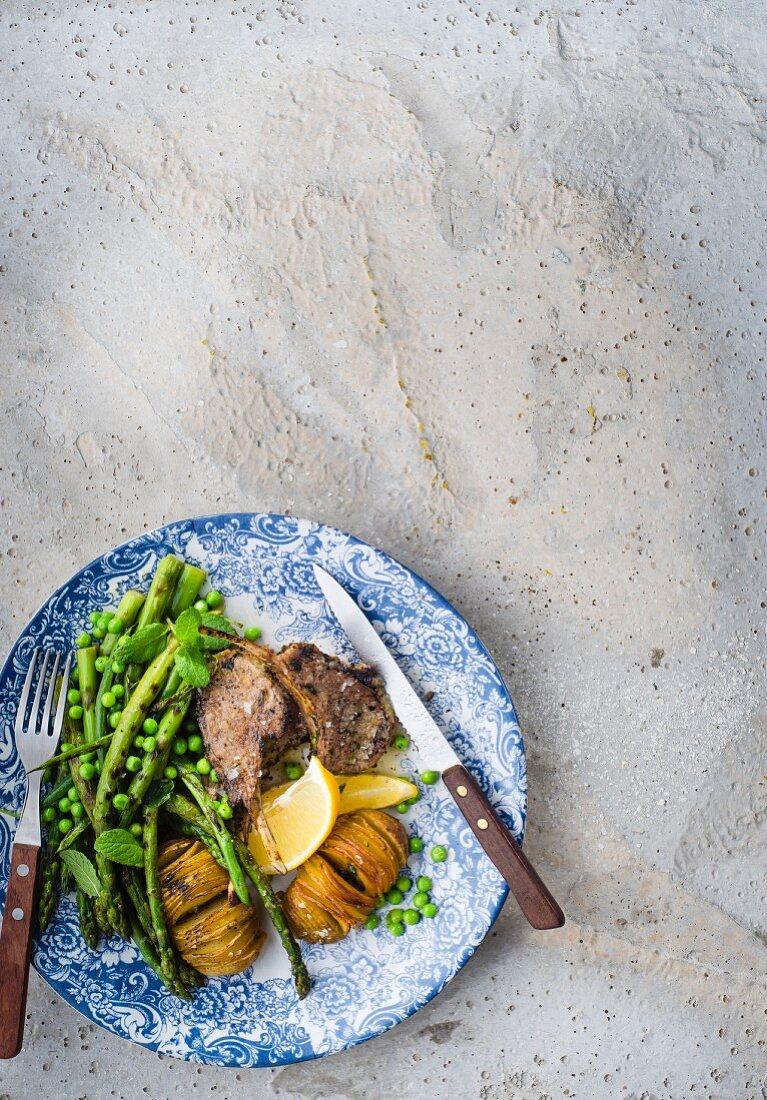 Lamb chops on potatoes, asparagus and peas