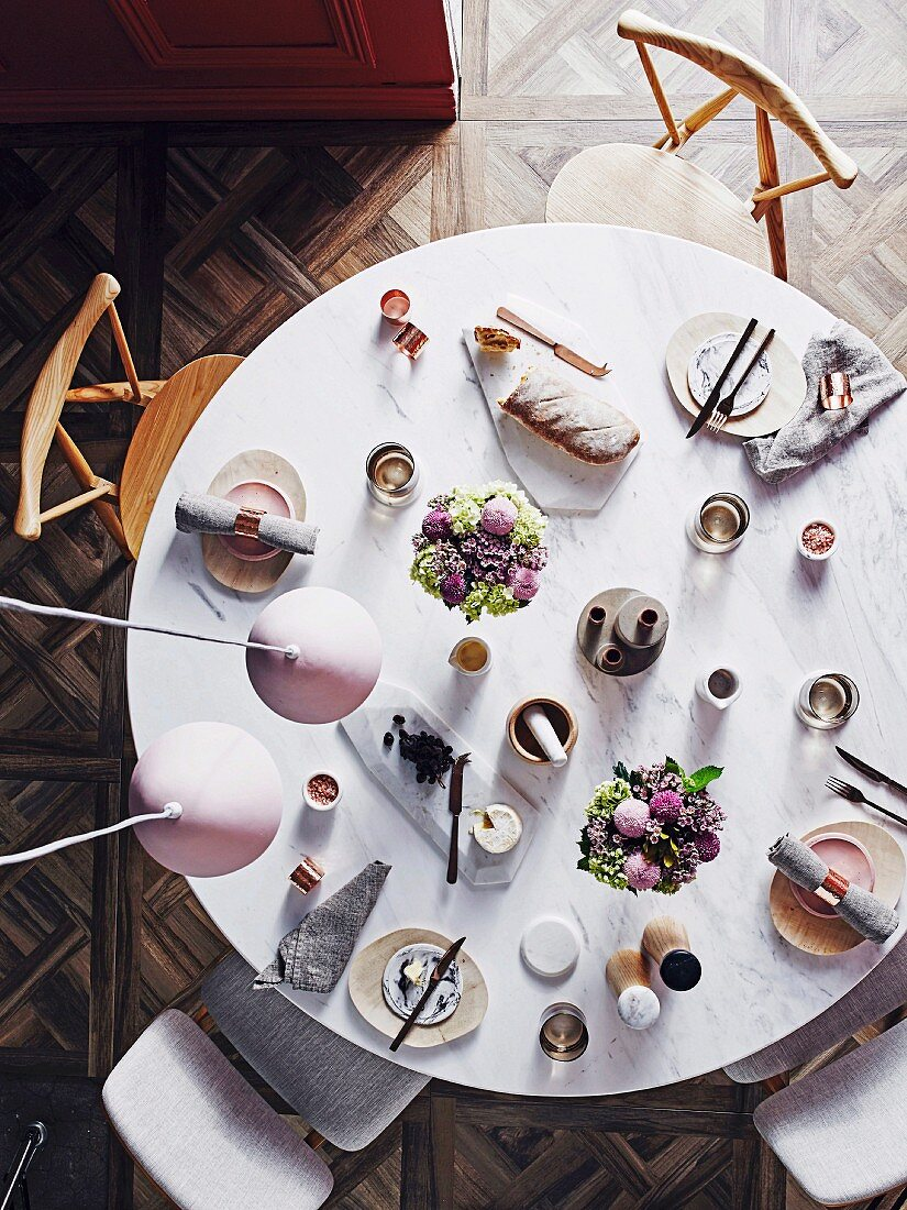 Laid round marble table with pastel colored floral decoration from a bird's eye view
