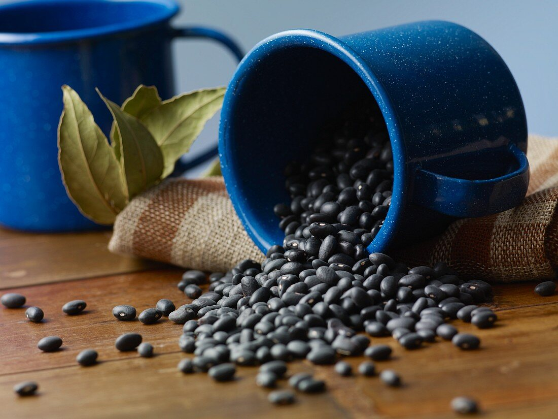 Black beans falling from an enamel mug