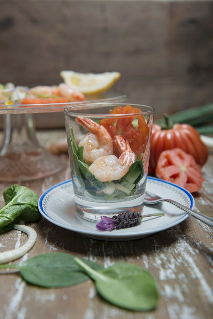 King prawns on a spinach salad in a glass with beefsteak tomatoes, spring onions and lemons in the background