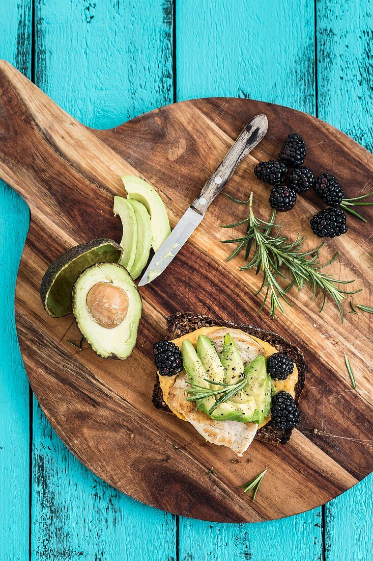 A slice of bread topped with omelette, avocado, blackberries and rosemary