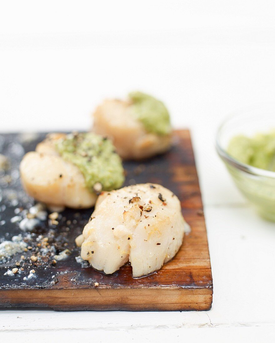 Scallops grilled on a cedar wood plank with avocado pesto