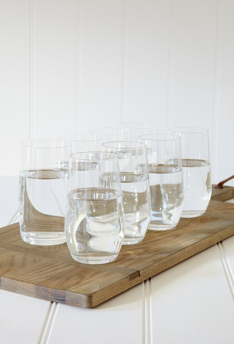 Glasses of water on a chopping board