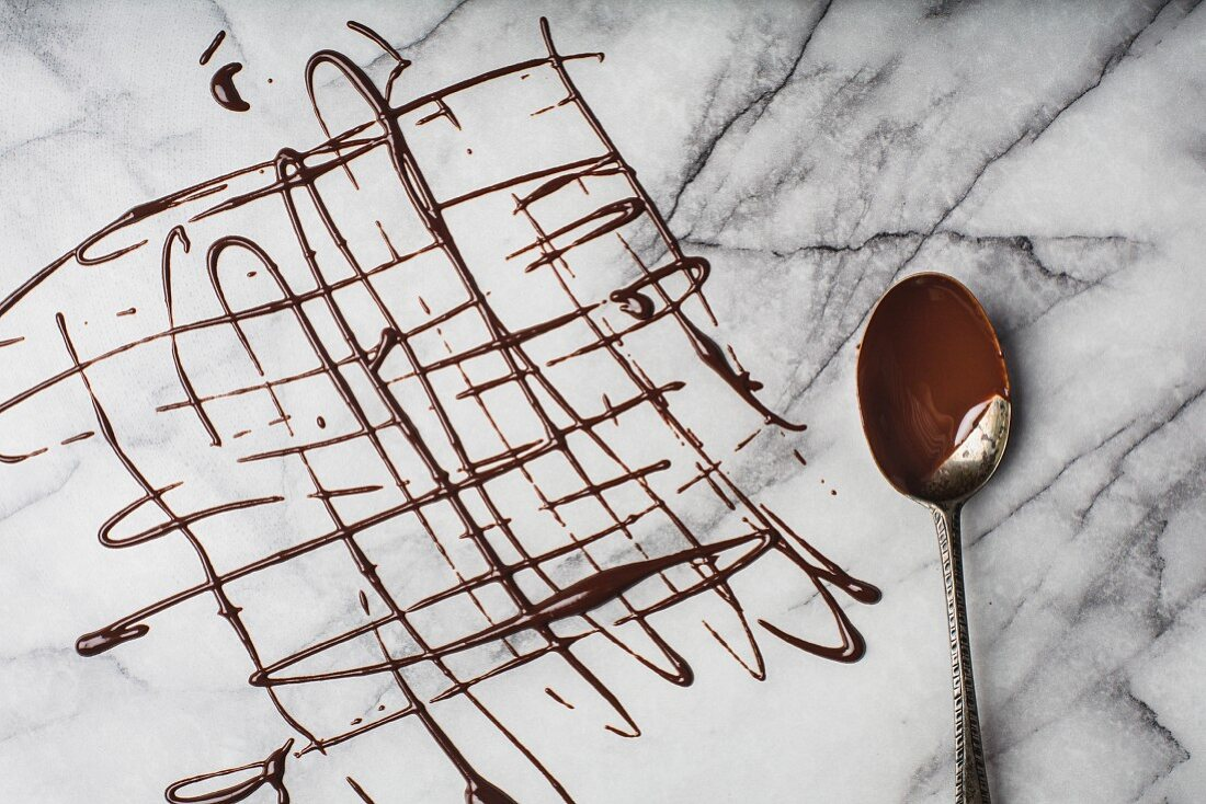 A lattice of melted organic dark chocolate on marble surface