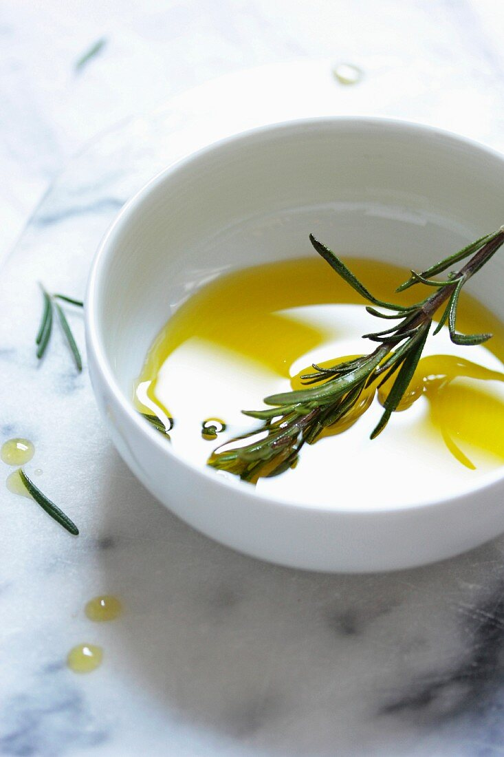 Olive oil and rosemary in a white bowl