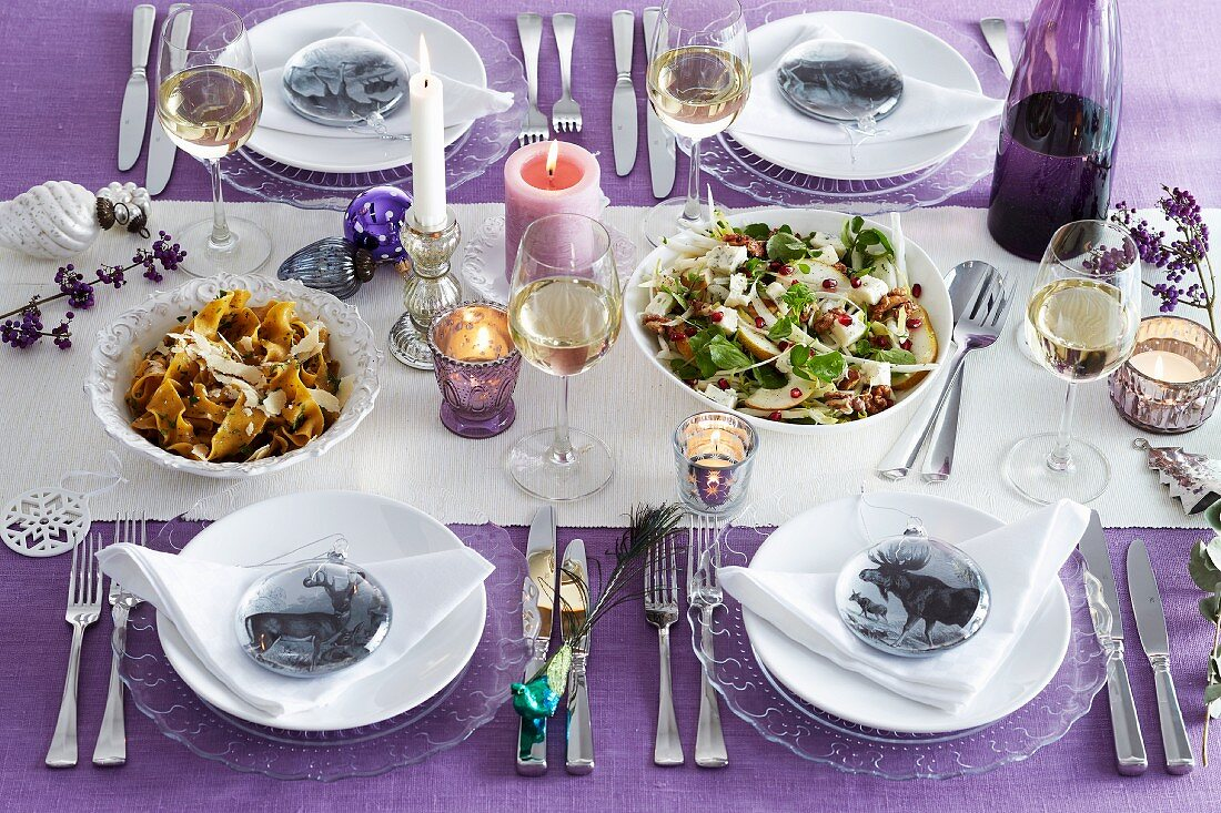 Table laid for Christmas in purple with various dishes, glasses of white wine and animal place setting decorations