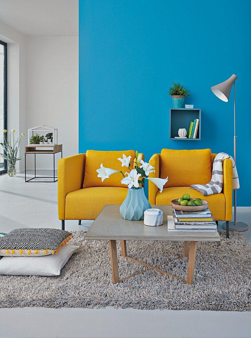 Zwei senfgelbe Polstersessel vor blauer Wand, Couchtisch mit Betonplatte auf Hochflorteppich