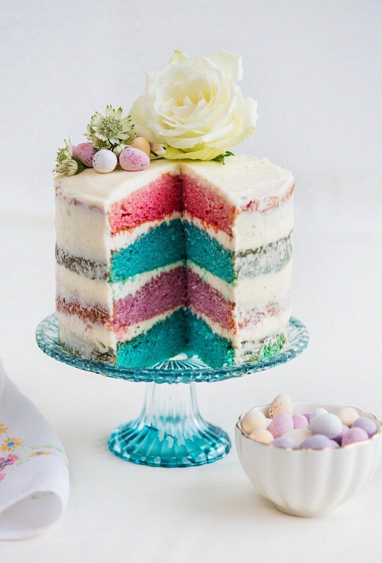 Vierschichtiger Rainbow Cake mit weißem Zuckerguss, Ostereiern und Blumendeko (angeschnitten)