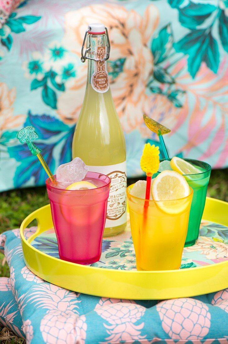Bunte Gläser und Flasche mit Sommerdrinks auf einem Tablett