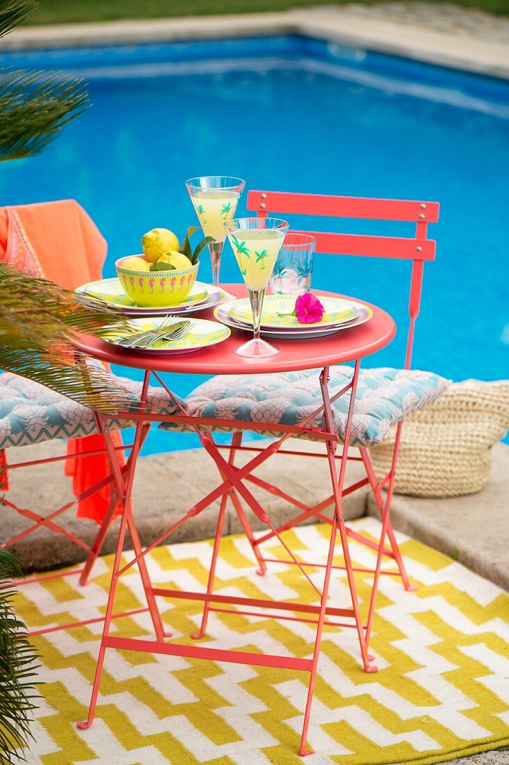 Red metal table and chairs on rug in colourful seating area next to pool