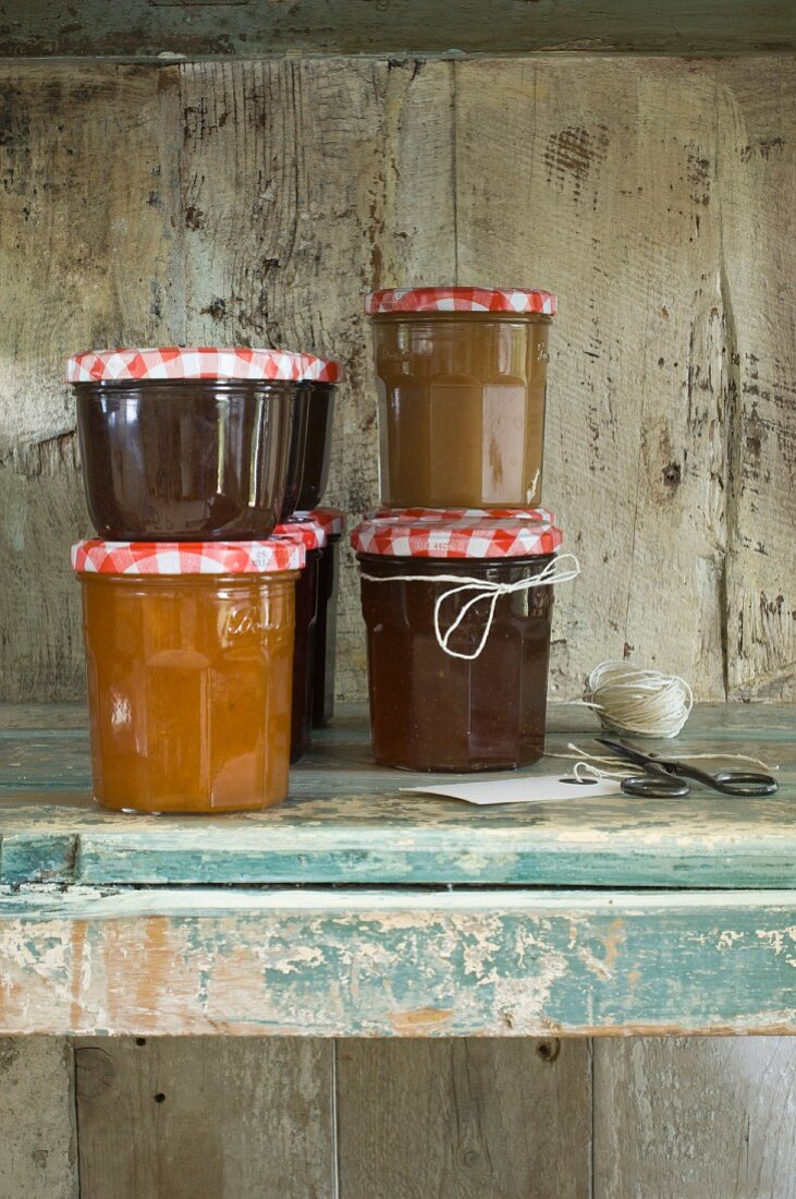 Jars of jam stacked in a rustic wooden cupboard