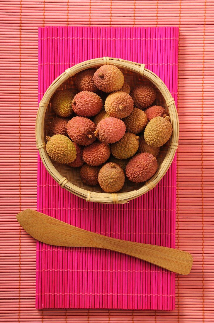 Fresh lychees in a bamboo basket (seen from above)