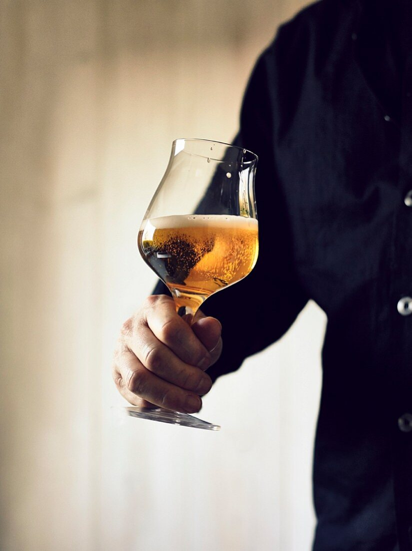 A man holding a glass of India Pale Ale