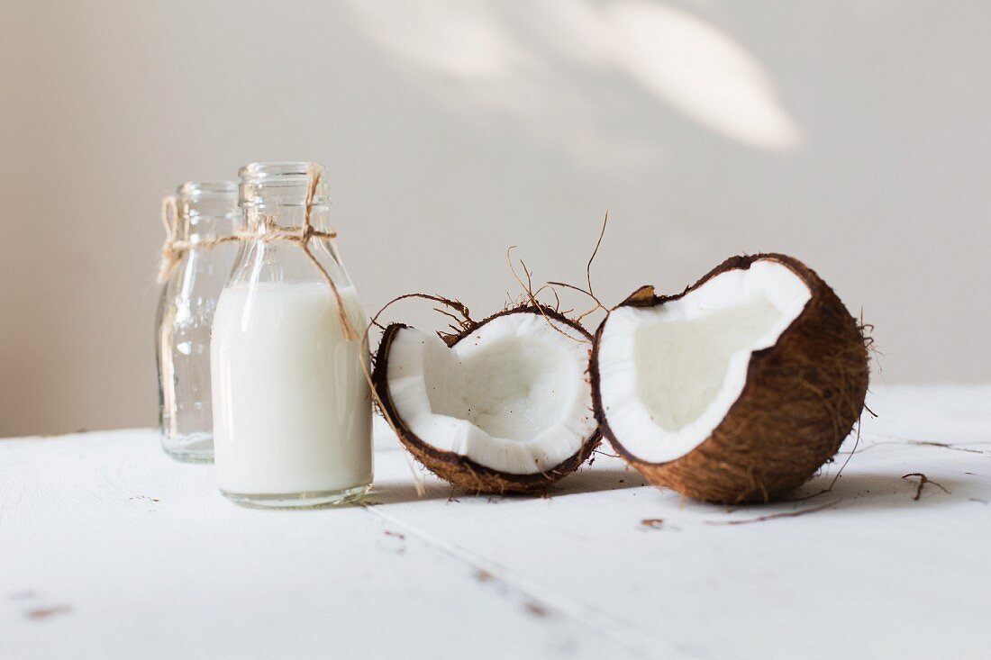 An open coconut and a bottle of coconut milk