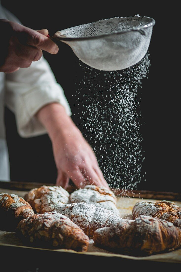 Croissants being dusted with icing sugar