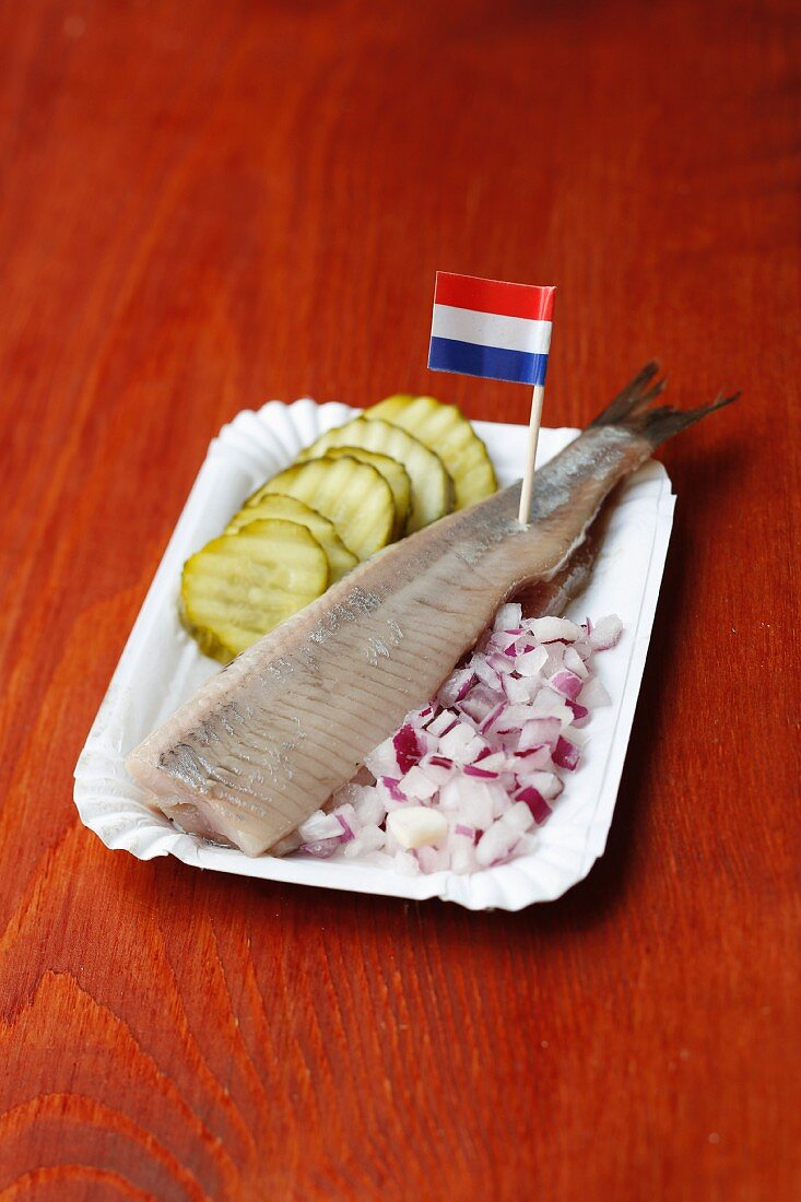 Soused herring with diced onion and pickled cucumber on a paper plate