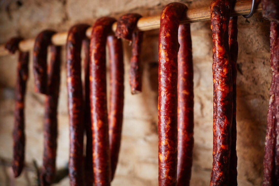Air dried salsiccia hanging from a wooden bar