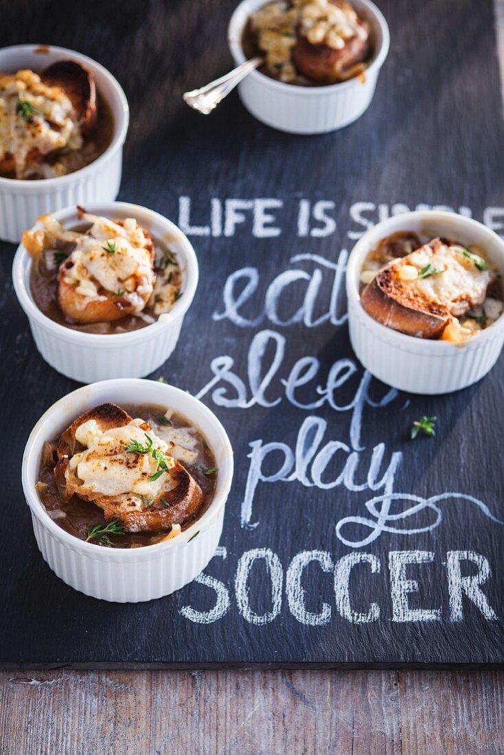 Mini bowls of French onion soup on a slate