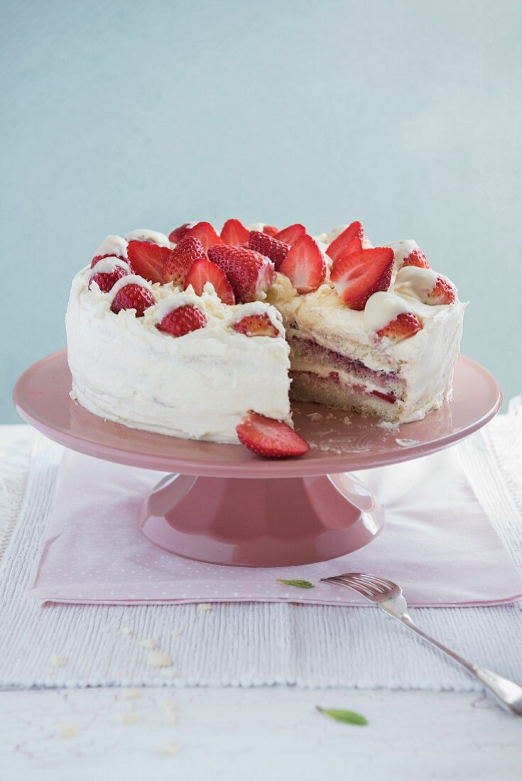 White chocolate and strawberry cake on a cake stand, sliced