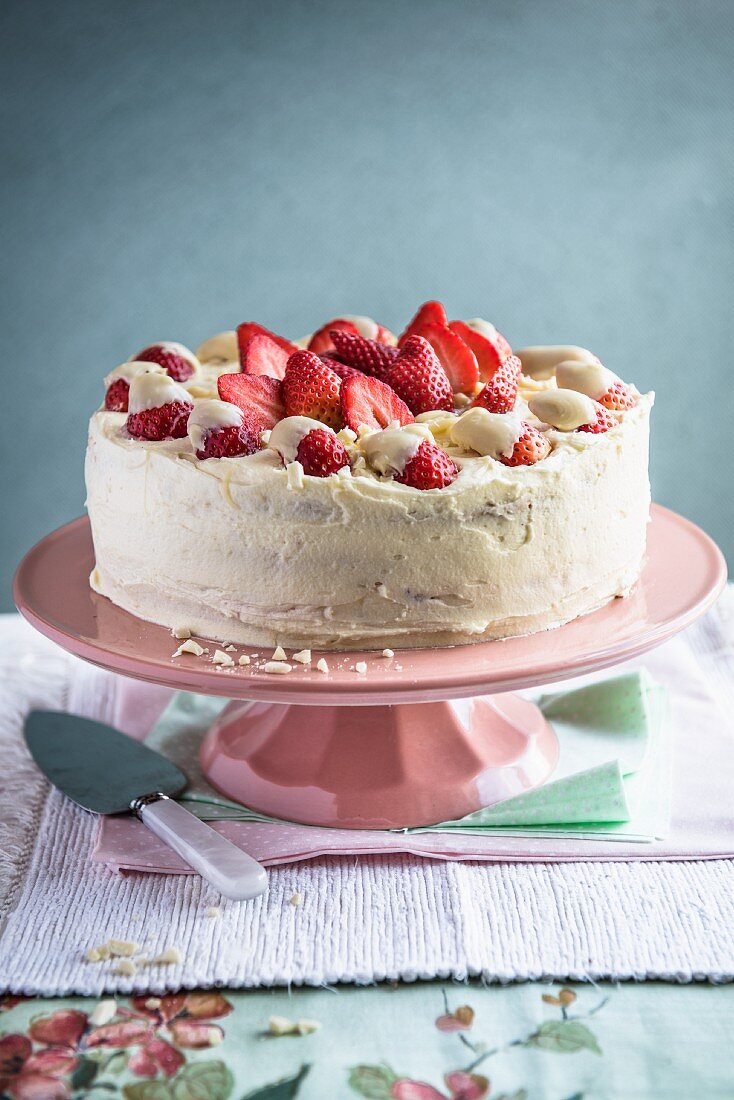 A white chocolate and strawberry cake on a cake stand