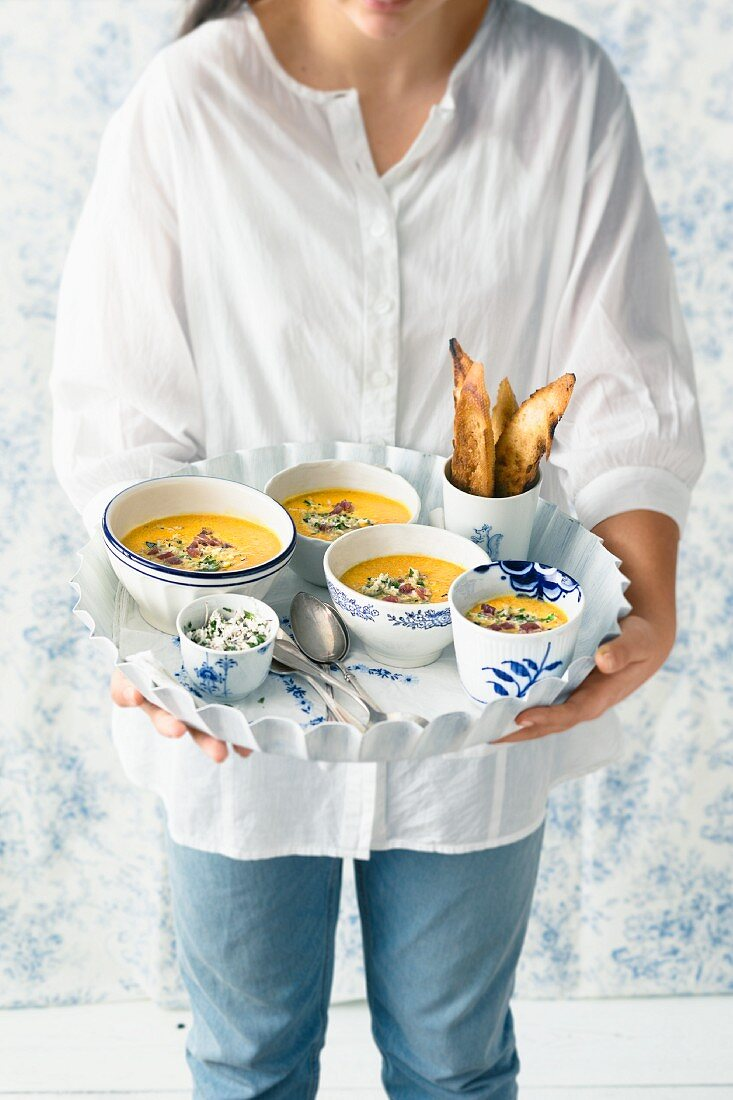 A woman holding carrot and ginger soup with coconut sambal on a tray