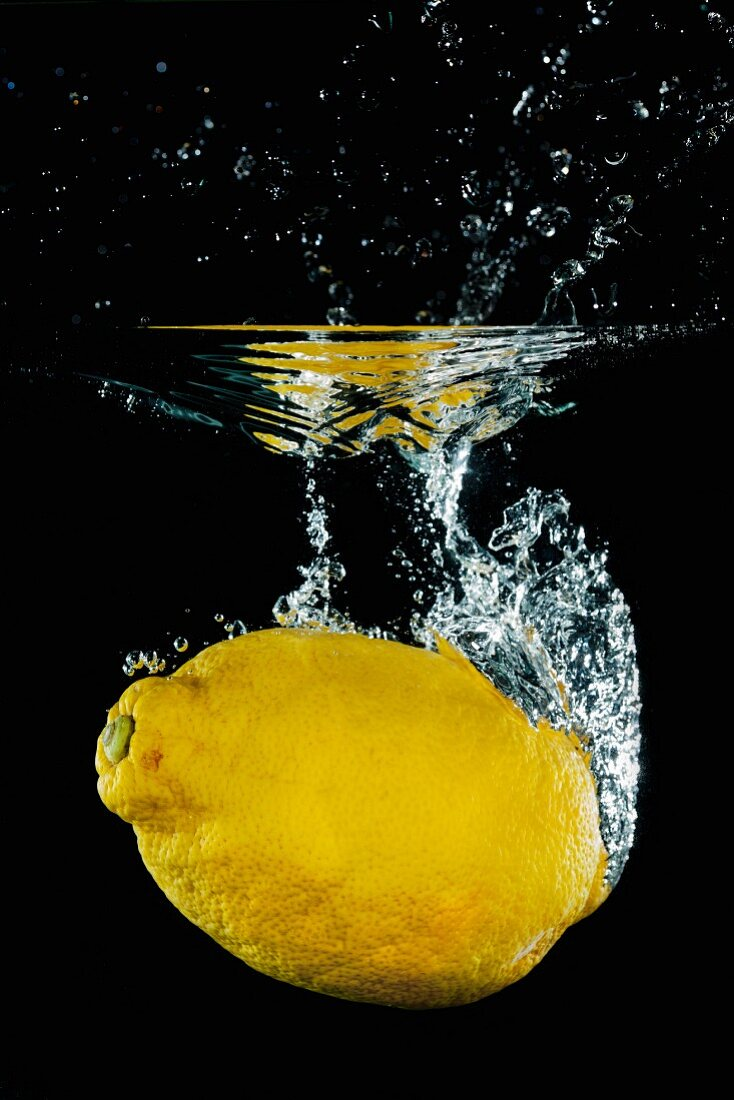 A lemon falling into water with a splash