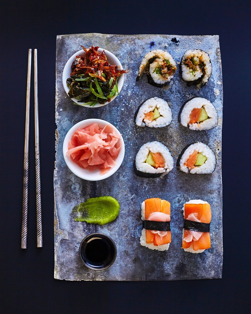 A sushi platter with wasabi, pickled ginger and salad