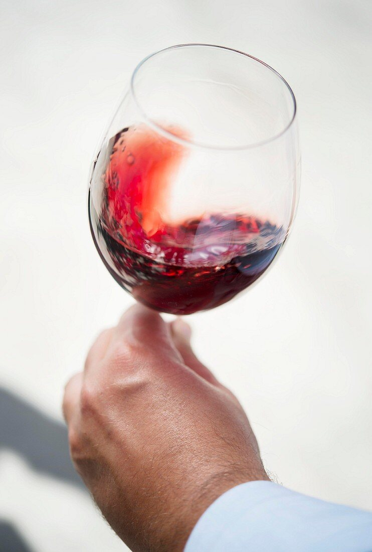 A hand holding a glass of red wine