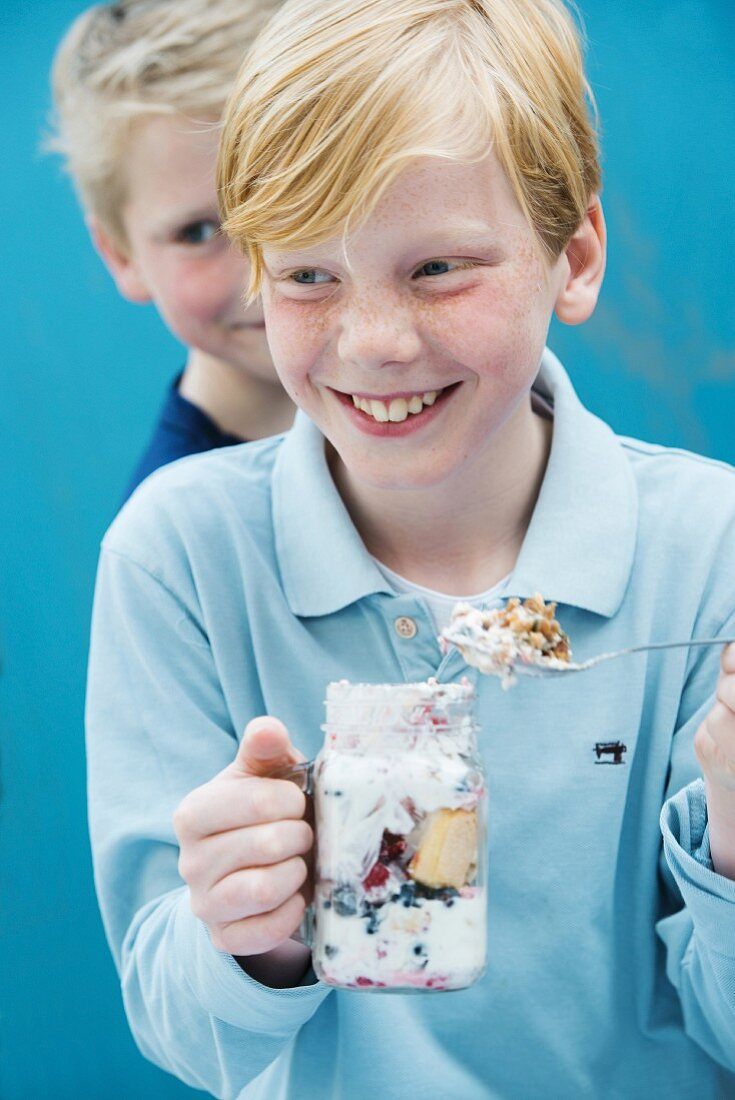 A boy eating yoghurt muesli with berries from a glass