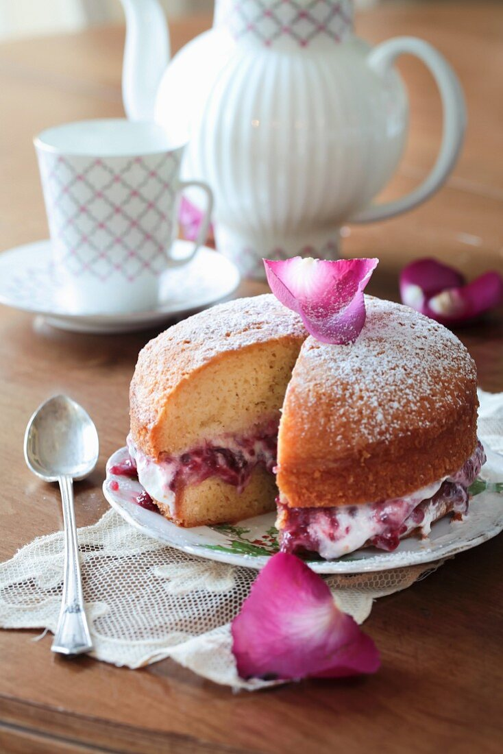 A Victoria Sandwich Cake with berry jam and rose petals